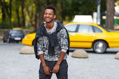 Smiling young man mixed race standing outside on street. Portrait of happy man standing outside on street. royalty free stock photography
