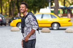 Profile portrait of a funny young man in casual clothes, walking in day time,  on blurred street background. royalty free stock images