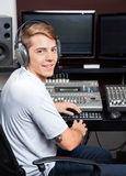 Smiling Young Man Mixing Audio In Recording Studio Stock Photos