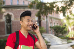 Smiling young man on mobile phone. A handsome,smiling young man on a mobile phone outdoors Royalty Free Stock Images