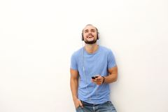 Smiling young man with mobile phone and headphones. Portrait of a smiling young man with mobile phone and headphones Stock Photos