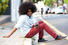 Smiling young man with mobile phone sitting on sidewalk. Full body portrait of smiling young man with mobile phone sitting on sidewalk Royalty Free Stock Photo