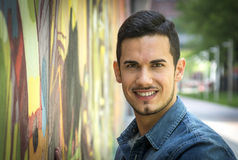 Smiling young man next to colorful graffiti wall Royalty Free Stock Photography
