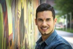 Smiling young man next to colorful graffiti wall. Looking at camera Royalty Free Stock Photography