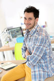 Smiling young man at office stock images