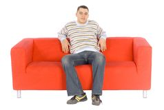 Smiling Young Man On Orange Couch Royalty Free Stock Photography