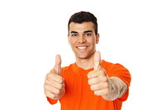 Smiling young man. In orange shirt shows you thumbs up Stock Photo