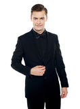 Smiling young man in party wear attire. Undoing coat button Stock Photo