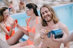 Smiling young man paying with credit card while resting with friends. At poolside stock photography