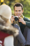 Smiling young man photographing woman in park Royalty Free Stock Photography