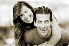 Smiling young man piggybacking his pretty girlfriend. Portrait of smiling young men piggybacking his pretty girlfriend in the park Royalty Free Stock Photography