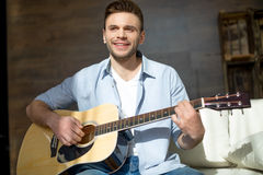 Smiling young man playing guitar and looking away. Handsome smiling young man playing guitar and looking away Royalty Free Stock Photos