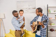 smiling young man playing guitar and looking at happy grandfather holding grandson stock images