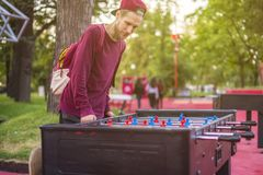 Smiling young man playing table soccer foosball outside having fun with friends d royalty free stock photos