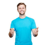 Smiling young man pointing at camera. Smiling young man in blue t-shirt pointing at the camera with two hands against a white background royalty free stock image