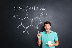 Smiling young man pointing on drawn caffeine molecule chemical structure Stock Photography