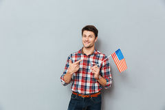 Smiling young man pointing on United States of America flag Stock Images