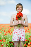 Smiling young man with poppies Royalty Free Stock Image