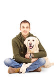 Smiling young man posing with a retriever dog. Isolated against white background Royalty Free Stock Photography