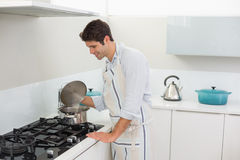Smiling young man preparing food in the kitchen Stock Photos