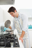 Smiling young man preparing food in kitchen Royalty Free Stock Photos