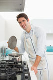 Smiling young man preparing food in kitchen Royalty Free Stock Photo