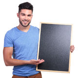 Smiling young man presenting a blackboard Stock Photos