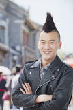 Smiling Young man with punk Mohawk and arms crossed, portrait royalty free stock images