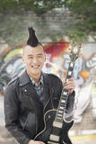 Smiling Young man with punk Mohawk holding guitar stock photos