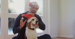 Smiling young man putting santa cap on his pet dog 4K 4k