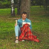 Smiling Young Man reading book outdoor with a warm red plaid and a cup of tea on background Autumn vacations and Lifestyle concept stock image