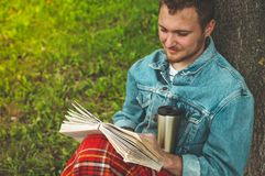 Smiling Young Man reading book outdoor with a warm red plaid and a cup of tea on background Autumn vacations and Lifestyle concept royalty free stock image