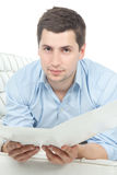 Smiling young man reading documents over white Royalty Free Stock Images