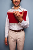 Smiling young man reading a red book Stock Photos