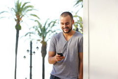 Smiling young man reading text message on mobile phone Royalty Free Stock Photos