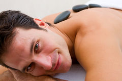 Smiling young man receiving hot stone treatment Royalty Free Stock Photography