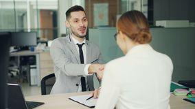 Smiling young man recruiter is talking to young woman successful candidate then shaking her hand during job interview in