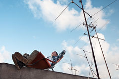 Smiling young man resting in the chair at the edge of the roof in the city. Cheerful and smiling young man resting in the chair at the edge of the roof in the Stock Image