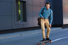 Smiling young man riding longboard. And using smartphone royalty free stock photo