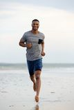 Smiling young man running barefoot Royalty Free Stock Image