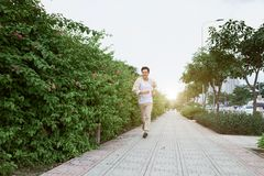 Smiling young man running in the park during summer.  stock images