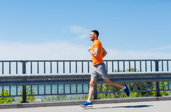 Smiling young man running at summer seaside Stock Photo