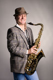 Smiling young man with a saxophone. Royalty Free Stock Photography