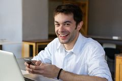 Smiling young man sending text message on mobile phone Stock Image