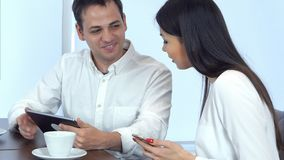 Smiling young man sharing something funny on his tablet with female coworker holding phone during lunch. Smiling young men sharing something funny on his tablet stock photos