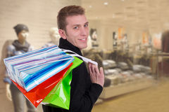 Smiling young man with shopping bags in a clothing store Stock Photo
