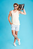 Smiling young man in shorts, hat and sunglasses holding boombox. Full length of smiling young man in shorts, hat and sunglasses holding boombox Stock Photography