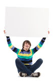 Smiling young man showing blank placard. Stock Photo