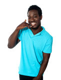Smiling young man showing calling gesture Royalty Free Stock Images