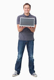 Smiling young man showing his laptop screen Royalty Free Stock Images